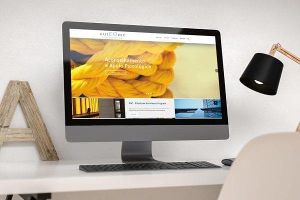 Desktop numa mesa com layout do site da empresa outCOme